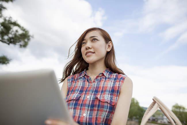 Tiefansicht einer jungen Frau mit digitalem Tablet im Park. — Stockfoto