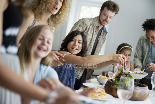 Family of adults and children gathering around dinner table. — Stock Photo