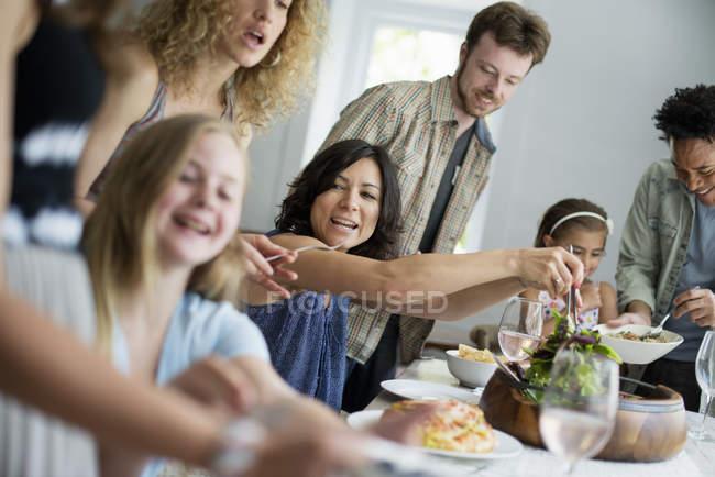Familia de adultos y niños reúne alrededor de la mesa - foto de stock