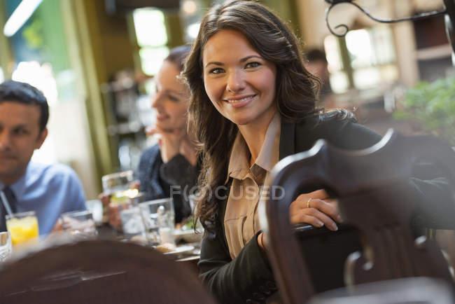 Junge Frau auf Stuhl gelehnt und suchen Sie in der Kamera, während der Sitzung in Bar mit Freunden — Stockfoto