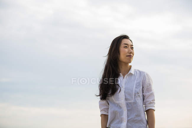 Mid adult woman in white blouse enjoying weather outdoors. — Stock Photo