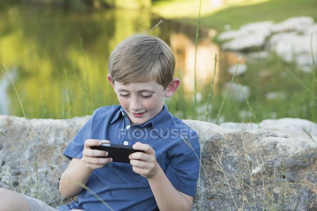Menino da idade elementar sentado na água e usando jogo eletrônico portátil . — Fotografia de Stock
