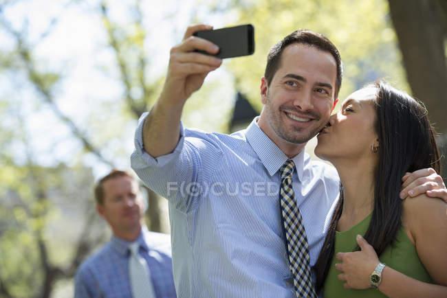 Paar unter Selfie mit Smartphone mit Mann im Hintergrund auf Stadt Straße — Stockfoto