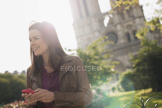 Женщина, держа смартфон и глядя на вид на экстерьер здания собора Нотр-Дам в Париже, Франция. — стоковое фото