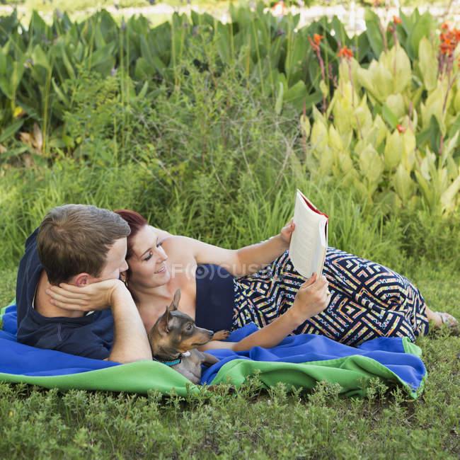 Mann und Frau relaxen auf blauem Teppich und lesen Buch mit Hund im Park. — Stockfoto