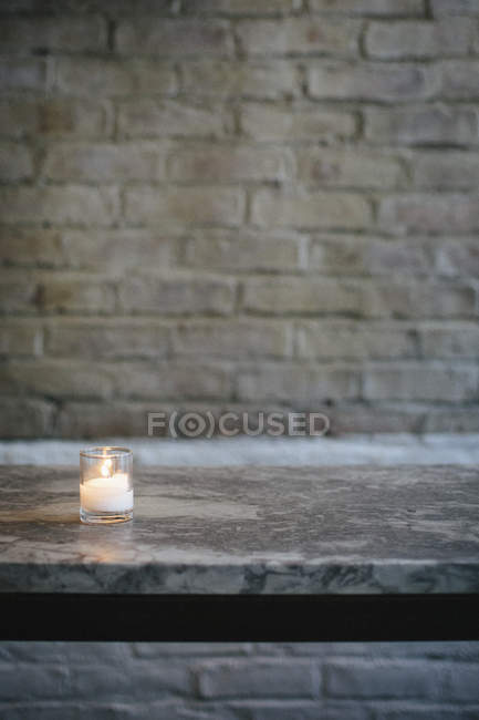 Lit candle on marble bench against brick wall. — Stock Photo