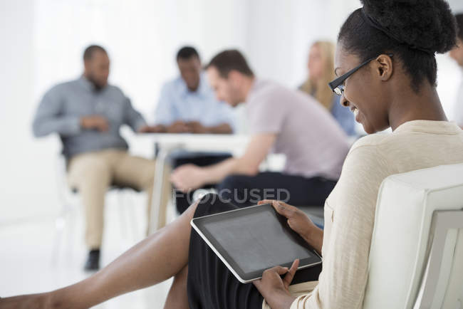 Woman sitting and holding digital tablet in office with group of people at business meeting. — Stock Photo