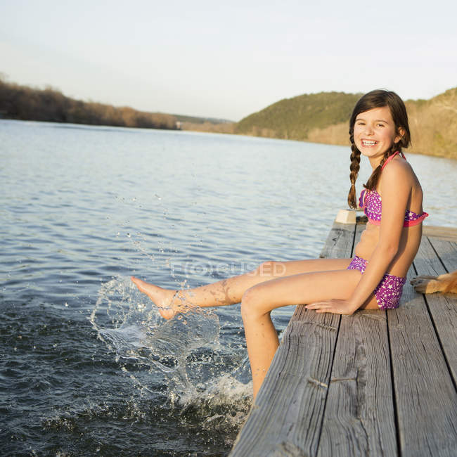 Pre-adolescent girl in bikini sitting on jetty with feet in water. — Stock Photo