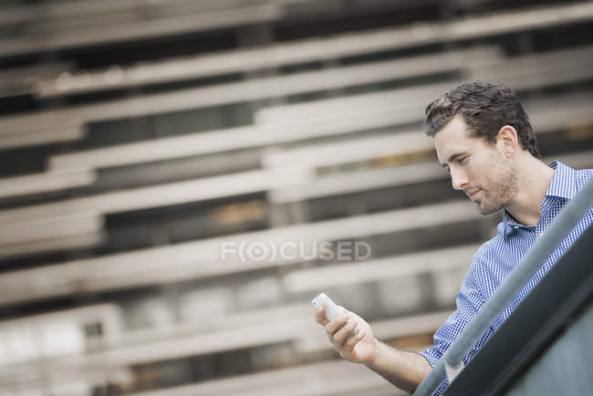 Young man standing on street and checking smartphone, low angle view. — Stock Photo