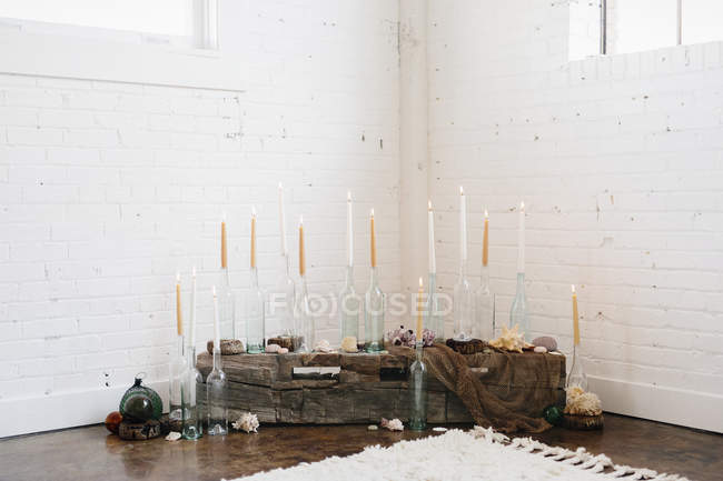 Tall lit candles in clear glass bottles arranged in corner. — Stock Photo