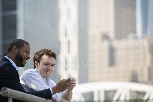 Due uomini d'affari che guardano lo smartphone mentre si appoggiano alla ringhiera in centro . — Foto stock