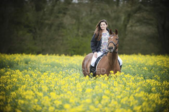 Mulher montando cavalo marrom através de culturas de mostarda amarelo florido no campo rural . — Fotografia de Stock