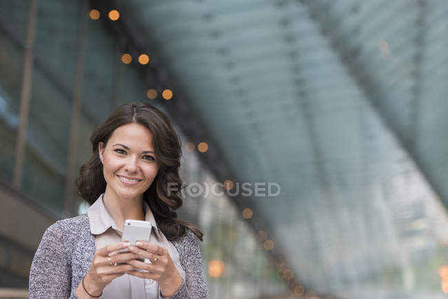 Young businesswoman in grey cardigan using smartphone and smiling. — Stock Photo