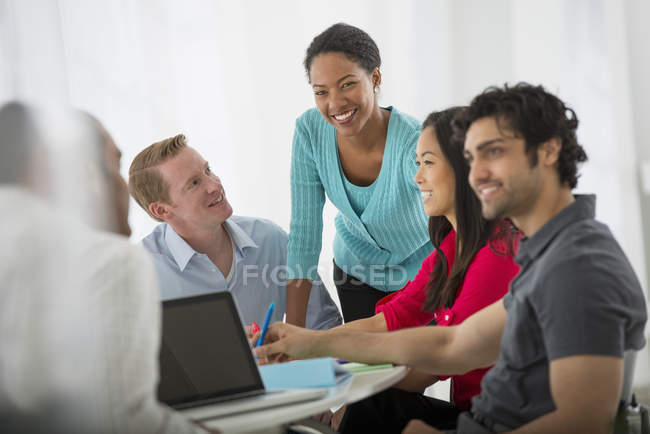 Multi ethnic group of people around table with laptop in meeting room in office. — Stock Photo