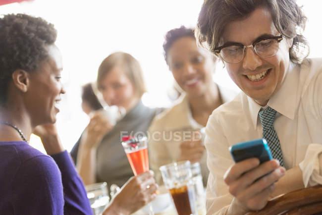 Человек проверяет смартфон на встрече с друзьями в ресторане . — стоковое фото