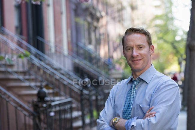 Man in blue shirt and tie with arms folded standing on sidewalk outside house. — Stock Photo