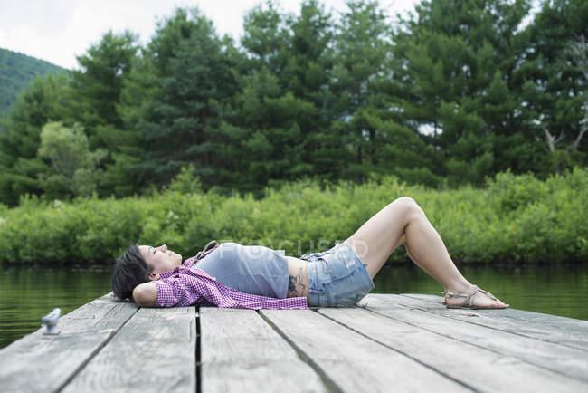 Mujer acostada en un embarcadero de madera junto al lago con las manos detrás de la cabeza . - foto de stock