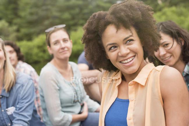 Jeune femme avec afro souriant en groupe d'amis à l'extérieur . — Photo de stock