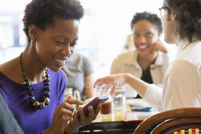 Женщина проверяет смартфон на встрече с друзьями в ресторане . — стоковое фото