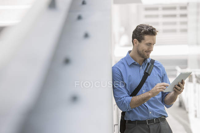 Young man with bag strap using digital tablet in urban scene. — Stock Photo