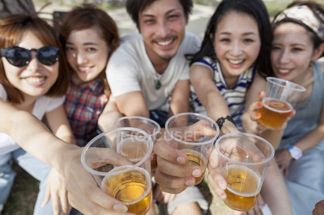 Group of cheerful Asian friends toasting with beer in park. — Stock Photo
