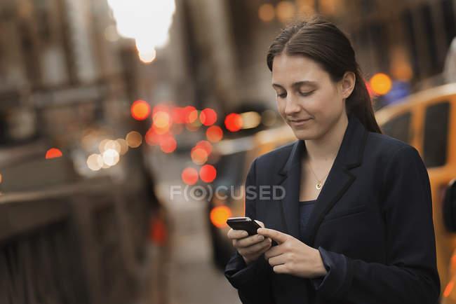 Geschäftsfrau checkt in der Abenddämmerung ihr Handy auf dem Bürgersteig der Stadt. — Stockfoto