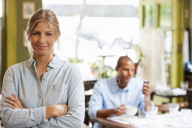 Woman standing with arms folded in cafe interior with man using phone in background. — Stock Photo
