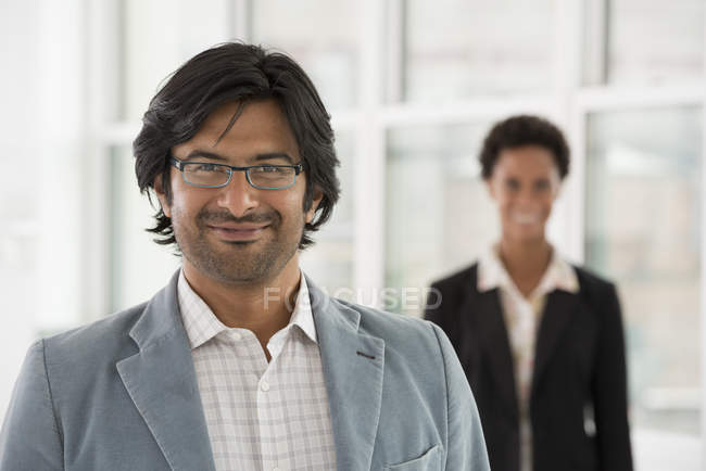 Mature man and mid adult woman standing in office and looking in camera. — Stock Photo