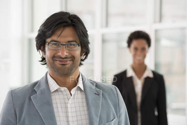 Maduro homem e médio adulto mulher de pé no escritório e olhando no câmara . — Fotografia de Stock
