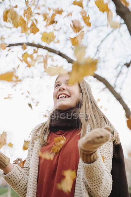 Allegro adolescente ragazza gettando foglie autunnali in aria nel parco . — Foto stock