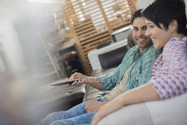 Couple assis sur le canapé à la maison et en maintenant le dispositif de commande à distance. — Photo de stock