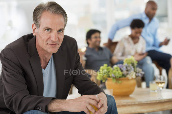 Mature man with wine sitting away from group of people at indoor party in background. — Stock Photo