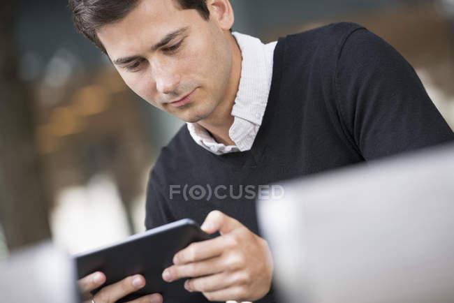 Крупным планом молодой человек сидел на улице и с помощью цифрового планшета — стоковое фото
