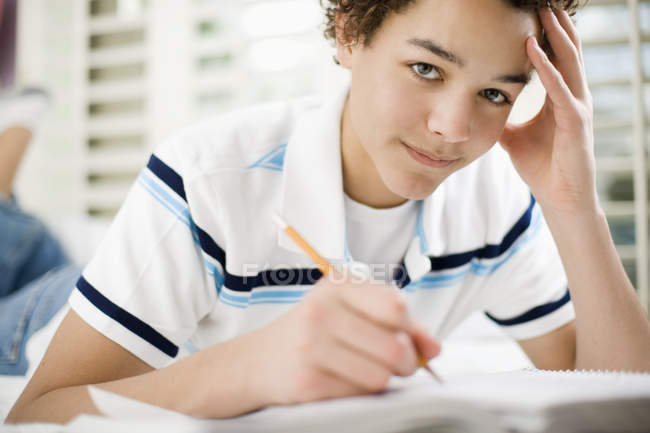 Pre-adolescent boy lying on front on bed and writing in school book. — Stock Photo