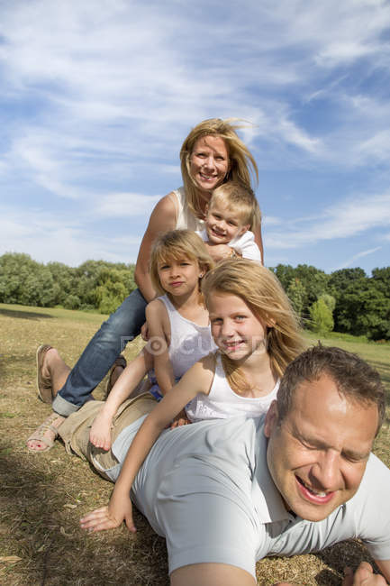 Father and mother with children playing in park. — Stock Photo