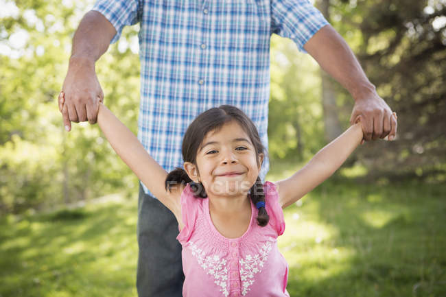 Father holding hands with elementary age daughter in park. — Stock Photo