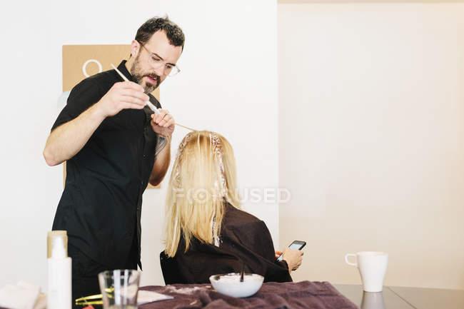 Maschio parrucchiere utilizzando stagnola mentre tinge i capelli biondi del cliente femminile con smartphone . — Foto stock