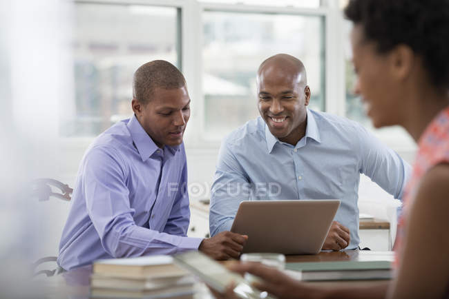 Three people working around office table and using digital tablet and laptop. — Stock Photo