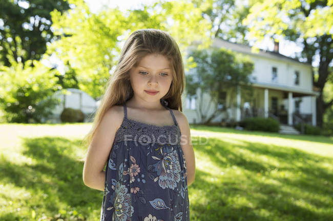 Little girl standing in garden with hands behind back. — Stock Photo