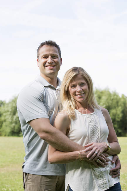 Mid adult man and woman standing smiling and embracing in park. — Stock Photo