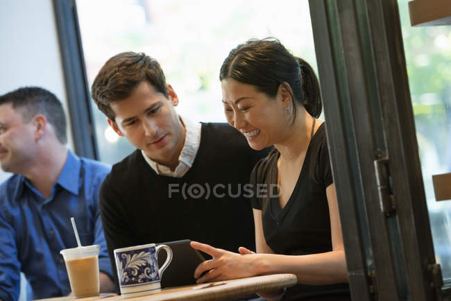 Group of people sitting around  table in coffee shop with drinks and using digital tablet. — Stock Photo