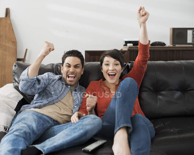 Man and woman sitting, celebrating and pumping air with fists while watching tv on sofa. — Stock Photo