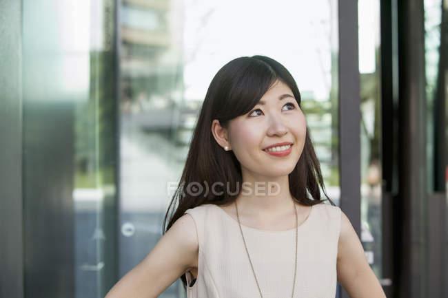 Porträt einer jungen Frau, die in einem Bürogebäude nach oben blickt. — Stockfoto