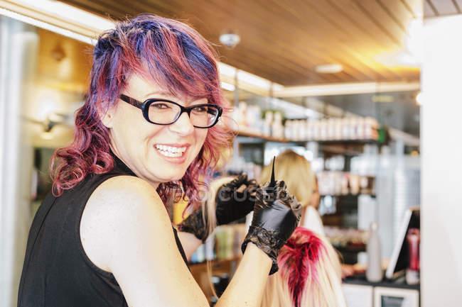 Colorista per capelli in guanti sorridente in macchina fotografica mentre applica la tintura per capelli rossi ai capelli biondi del cliente . — Foto stock