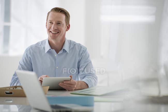 Бізнесмен, сидячи і проведення цифровий планшетний в просторі офісу. — стокове фото