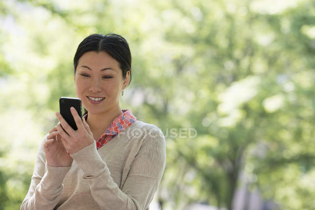 Mid adult woman checking smartphone in city park. — Stock Photo