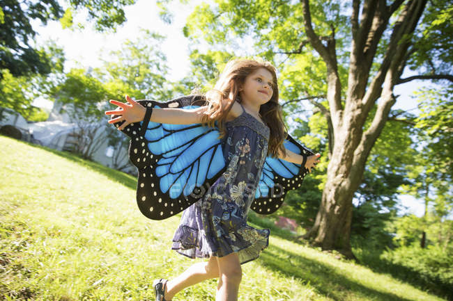Little girl running across lawn wearing blue butterfly wings with arms outstretched. — Stock Photo
