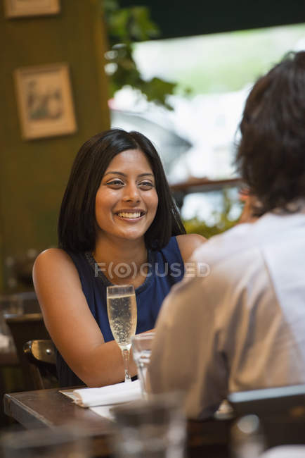 Couple sitting at cafe table smiling and looking at each other. — Stock Photo