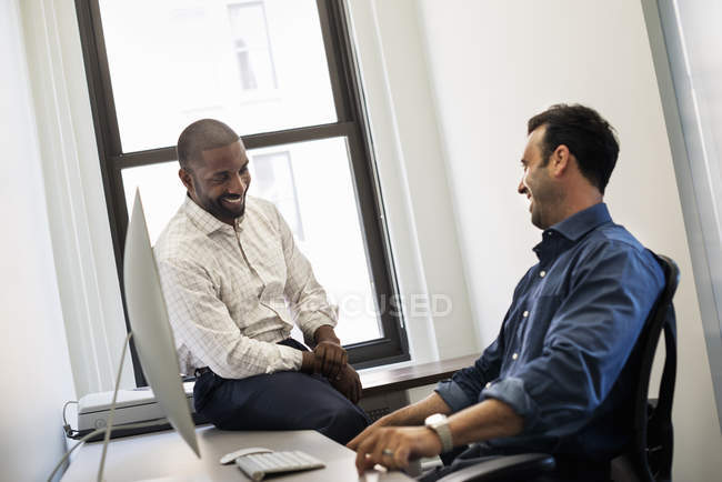 Man leaning back in office chair and talking to colleague sitting on desk. — Stock Photo
