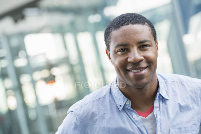 African american man in blue shirt standing in front modern building and smiling. — Stock Photo